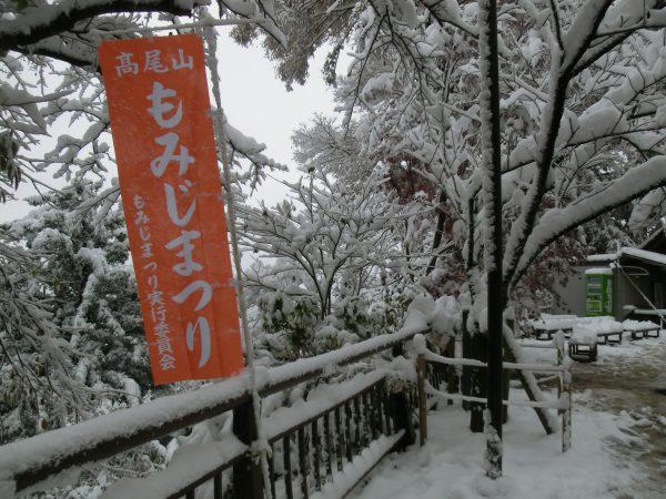 『もみじまつり』の旗は色鮮やかだが、その後ろのもみじはまっ白。高尾山口駅近くのもみじは雪がちょっとかかって赤と白とできれいでしたけど。